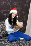 Caucasian girl in santa hat with gift Stock Photography