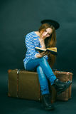 Caucasian girl sitting on a suitcase. Caucasian girl reading a book while sitting on a suitcase Royalty Free Stock Image