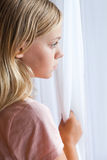 Caucasian girl standing near a window Stock Photography