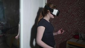 Caucasian girl in VR glasses is surprised and keeps her hand near mouth. Watching movie stock footage