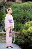 Caucasian girl wearing a kimono. Beautiful caucasian girl with a bright smile, wearing a pretty pink kimono in front of a Japanese pine tree Stock Photography