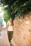 Caucasian girl in white T-shirt with fruits, green pants and gray sneakers is walking along a narrow ancient street with trees and. Blue shutters in the windows Stock Image