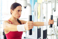 Caucasian girl is working out on butterfly machine at the gym Stock Photos