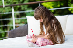 Caucasian girl writing at notepad Royalty Free Stock Photography