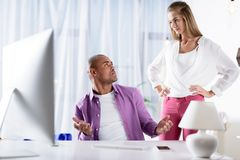 Caucasian girlfriend looking skeptically at african american boyfriend. At computer stock image