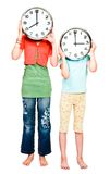 Caucasian girls holding clocks Royalty Free Stock Images