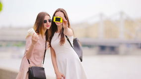 Caucasian girls making selfie background big bridge. Young tourist friends traveling on holidays outdoors smiling happy. Happy tourist couple, two girlfriends stock video