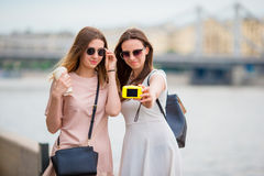 Caucasian girls making selfie background big bridge. Young tourist friends traveling on holidays outdoors smiling happy. Stock Photos