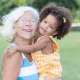 Caucasian grandma carrying her hispanic granddaughter. Portrait of a caucasian grandma carrying her little hispanic granddaughter Stock Photos
