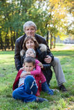 Caucasian grandparents walking with grandchildren in autumn park Royalty Free Stock Photos