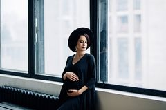 Caucasian gravid kvinna med smink i den svarta klänningen och den svarta hatten, stående av den framtida modern, lycklig havandes Royaltyfria Foton