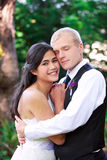 Caucasian groom holding his biracial bride, smiling. Diverse couple. stock photo