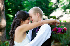 Caucasian groom holding his biracial bride, smiling. Diverse cou Royalty Free Stock Photos