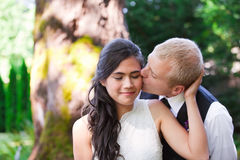 Caucasian groom lovingly kissing his biracial bride on cheek. Di Royalty Free Stock Photography