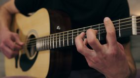 Caucasian guy in black T shirt playing on guitar. Close up of male hands playing on acoustic guitar. Professional