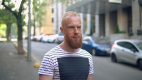 Caucasian guy in city. Bearded man goes along parked cars. smiling handsome male wearing casual t-shirt walking on the street summer season in town stock footage