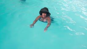 Caucasian hög kvinnlig åldring i bad för svart hatt i pölen för blått vatten i hotell Begreppet av rekreation på stock video