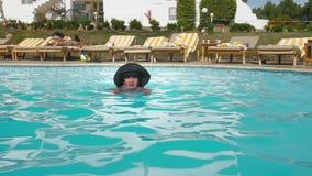Caucasian hög kvinnlig åldring i bad för svart hatt i pölen för blått vatten i hotell Mot bakgrunden av strandstolar stock video