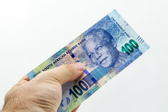 A Caucasian hand holding a hundred rand South African note with a plain background.  Stock Photography
