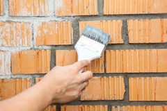 Caucasian hand starting to paint brick wall Royalty Free Stock Photo