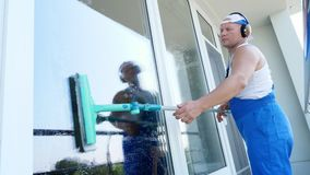 Caucasian handsome man, worker of cleaning service, in blue overalls, with headphones, , Cleaning, washing Windows by stock video footage
