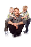 Caucasian happy father with two children sitting on the floor. Stock Photos