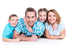 Caucasian happy smiling young family with two children. Lying down on the floor stock photos