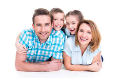 Caucasian happy smiling young family with two children. Lying down on the floor stock photography