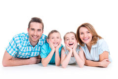 Caucasian happy smiling young family with two children. Lying down on the floor royalty free stock photos