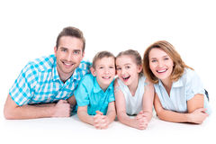 Caucasian happy smiling young family with two children. Lying down on the floor royalty free stock image
