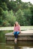 Caucasian High School Senior Girl Outside. One Caucasian High School Senior Girl Sitting on Dock at Lake Outside Summertime Stock Photo