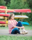 Caucasian High School Senior Girl Outside. One Caucasian High School Senior Girl wearing cold shoulder top Outside during Summertime. Kayak boats in background Royalty Free Stock Images