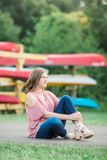 Caucasian High School Senior Girl Outside Sitting. One Caucasian High School Senior Girl wearing cold shoulder top Outside during Summertime. Kayak boats in Stock Images