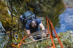 Caucasian hiker climbing on a safety chains through a very diffi Royalty Free Stock Images