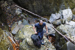 Caucasian hiker climbing on a safety chains through a very diffi Royalty Free Stock Image