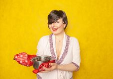Caucasian housewife prepares a meal. the brunette stands in a Bathrobe with a pan and pot holders on a yellow solid Studio backgro. Und alone stock images