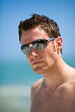 Caucasian hunk at the beach. Young handsome Caucasian man with sunglasses Stock Photo