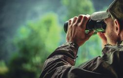 Camouflage and Binoculars. Caucasian Hunter in Camouflage with Binoculars Spotting Wildlife in the Remote Place. Hunting Theme royalty free stock image