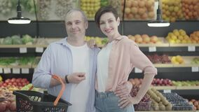 Caucasian husband and wife hugging and smiling at camera in grocery. Portrait of happy young beautiful brunette woman