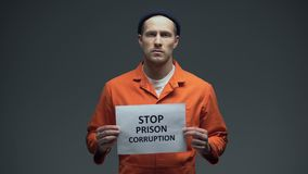 Caucasian imprisoned male holding Stop prison corruption sign, faulty system. Stock footage stock video