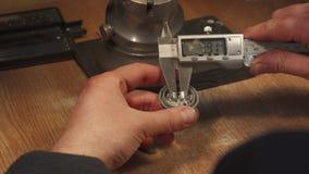 Jeweler measures zirconium gemstones. Caucasian jeweler measuring zirconium gemstones. Close up of male hands holding digital caliper over the table. Jewelry Stock Photo