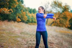 Caucasian jogger girl performs warming-up with hands  before jog Stock Image