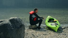 Caucasian kayaker on the lake shore stock video footage