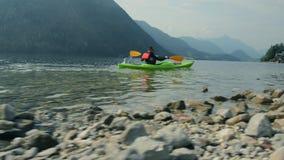Caucasian kayaker paddling on the lake stock video