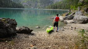 Caucasian kayaker on the scenic lake shore. Enjoying the view. Blindsee, Austria stock footage
