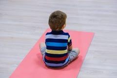 Caucasian kid exercising on yoga mats in gym, children sport. School royalty free stock photos