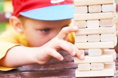 Caucasian kid is playing wood blocks tower game for practicing physical and mental skill. stock photos