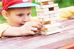 Caucasian kid is playing wood blocks tower game for practicing physical and mental skill. royalty free stock photos