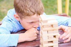 Caucasian kid is playing wood blocks tower game for practicing physical and mental skill. royalty free stock image