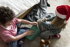 Caucasian kids unwrapping Christmas presents Stock Photos